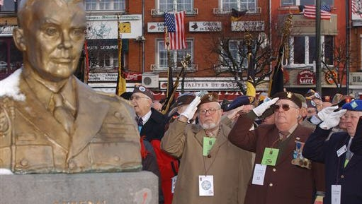 In this Dec. 18, 2004 file photo, U.S. and Belgian World War II veterans salute during a wreath laying ceremony at the General Anthony C. McAuliffe memorial in Bastogne, Belgium. The Battle of the Bulge, a last-ditch German offensive on Dec. 16, 1944 which was the bloodiest land battle of WWII involving US troops, who suffered some 80,000 casualties, including 19,000 killed. A tour taking place in December 2014 that's connected to the National World War II Museum in New Orleans is taking three dozen people to the battlefields and towns in Belgium where the Battle of the Bulge was fought 70 years ago.