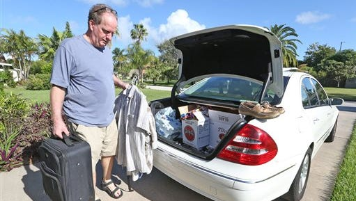 "Joe Roth, 53, of Cocoa, Beach, Fla.,  packs his family's car Wednesday, Oct. 5, 2016, as he prepares to evacuate himself and his wife, Debi, as Hurricane Matthew approaches Florida. ""I know when they tell you to get out, you go,"" Roth said."