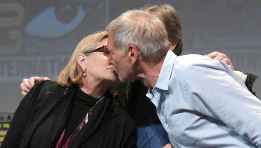 """FILE - In this July 10, 2015, file photo, Carrie Fisher, left, and Harrison Ford kiss at the Lucasfilm's """"Star Wars: The Force Awakens"""" panel on day 2 of Comic-Con International in San Diego, Calif. Fisher revealed in an interview with People magazine published online on Nov. 15, 2016, that she had an affair with Ford during the filming of the 1977 film, """"Star Wars."""""""