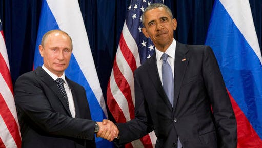 FILE - In this Monday, Sept. 28, 2015 file photo, U.S. President Barack Obama, right, and Russia's President President Vladimir Putin pose for members of the media before a bilateral meeting at the United Nations headquarters. President Barack Obama is promising that the U.S. will retaliate against Russia for its suspected meddling in America's election process, an accusation the Kremlin has vehemently denied. (AP Photo/Andrew Harnik)