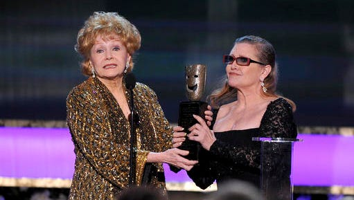"""FILE- In this Jan. 25, 2015, file photo, Carrie Fisher, right, presents her mother Debbie Reynolds with the Screen Actors Guild life achievement award at the 21st annual Screen Actors Guild Awards at the Shrine Auditorium in Los Angeles. Reynolds, star of the 1952 classic """"Singin' in the Rain"""" died Wednesday, Dec. 28, 2016, according to her son Todd Fisher. She was 84."""