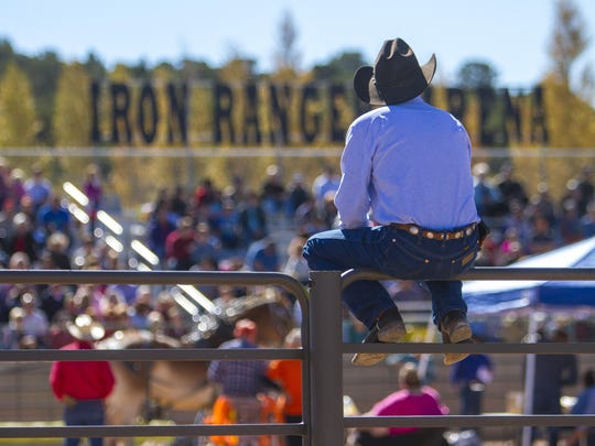 A man sits on a fence during an event at the 2015 Cedar Livestock & Heritage Festival.
