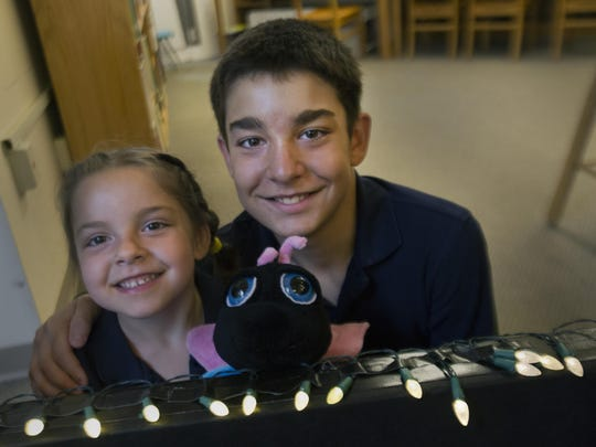 Alena Esposito, 6, who was cured of selective mutism, plays with puppets and her brother Kevin, 11, who also attends the Lighthouse Christian Academy.
