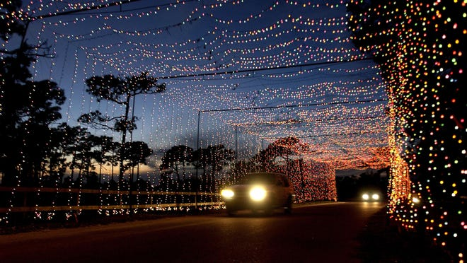12/24/05-- KATHLEEN HINKEL---- Cars move through a canopy of Christmas Lights at the Space Coast Lightfest in Wickham Park on Christmas Eve.