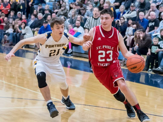 St. Philip's Zach Nelson (23) drives to the hoop as Climax-Scotts's Jake Lane (21) puts pressure. St. Philip and Climax-Scotts will be both be in action in district tournaments next week.