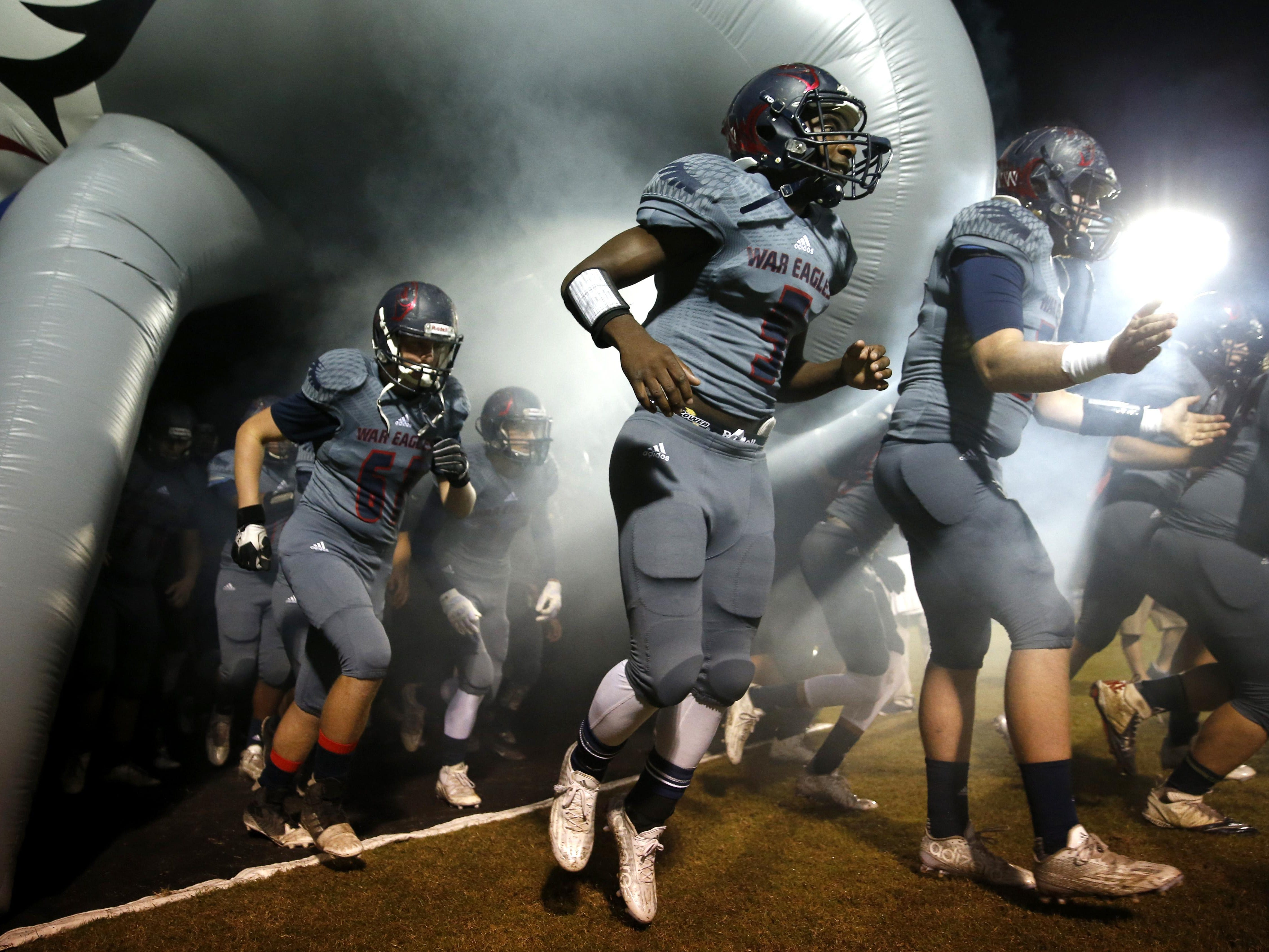 The Wakulla War Eagles charge out on to the field before their playoff game against Rickards in Wakulla on Friday.