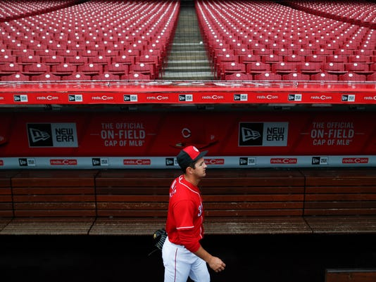 Cincinnati Reds pitcher Tyler Mahle walks through an empty dugout at Great American Ballpark, Thursday, March 29, 2018, in Cincinnati. Their first game of the regular season against the Washington Nationals was postponed until Friday due to weather. (AP Photo/John Minchillo)