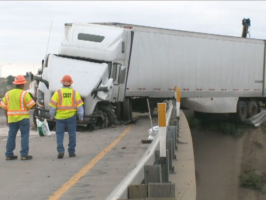 The semi-truck is hanging off of the I-25 bridge that goes over Highway 402.
