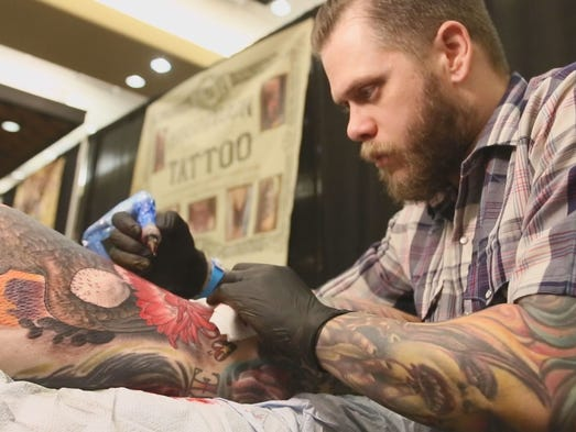 Chris Johns, known as Siege in the tattoo community, has been tattooing Vincent Rafferty of Phoenix for over six hours straight during the Northern Arizona Tattoo Fest in Prescott on July 4, 2014.