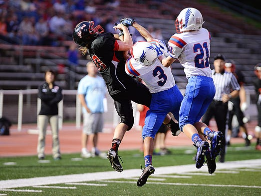 Alex Budde (#10) of the Rocori Spartans catches a pass near the end of the first period during Friday's game.