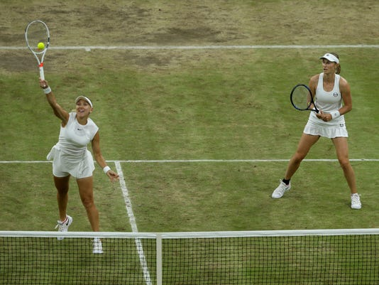Elena Vesnina of Russia, left, hits a return watched by her compatriot Ekaterina Makarova, to Romania's Monica Niculescu, and Taiwan's Hao-Ching Chan in the Women's Doubles final match on day twelve at the Wimbledon Tennis Championships in London Saturday, July 15, 2017. (AP Photo/Tim Ireland)