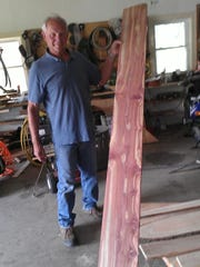 Vern Salzl proudly displays a cedar board he made on his portable sawmill.