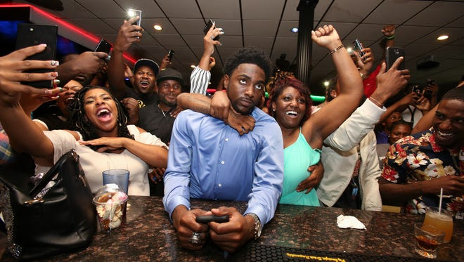 WKU's Taywan Taylor, center, was surrounded by his mom La'Tashia Majors, right, and other elated family and friends after being selected as the 72nd pick in the third round of the NFL draft by the Tennessee Titans during a watch party at Vis a Vis Bar and Grill.  His dad Terrance Taylor, Sr., was at left with black cap.