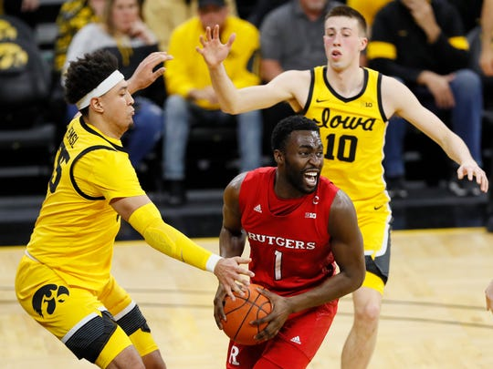 Rutgers forward Akwasi Yeboah (1) drives between Iowa's Cordell Pemsl, left, and Joe Wieskamp, right, during the first half of an NCAA college basketball game, Wednesday, Jan. 22, 2020, in Iowa City, Iowa. (AP Photo/Charlie Neibergall)