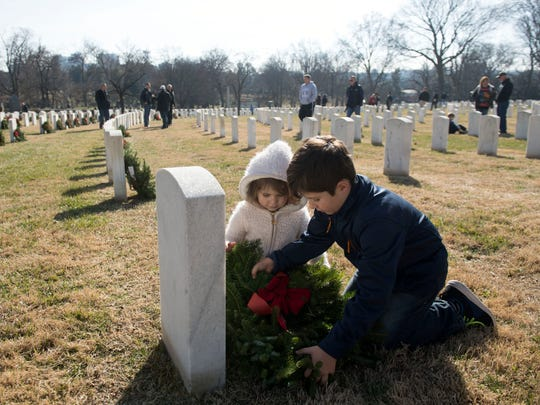 Siblings Lacey, left, and Trey Levert lay a wreath at the grave of Raymond Gallagher at Knoxville National Cemetery for Wreaths Across America on Saturday, December 16, 2017.