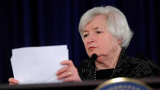 Federal Reserve Chair Janet Yellen gathers her papers at the conclusion of a news conference at the Federal Reserve in Washington on Wednesday, June 18, 2014.