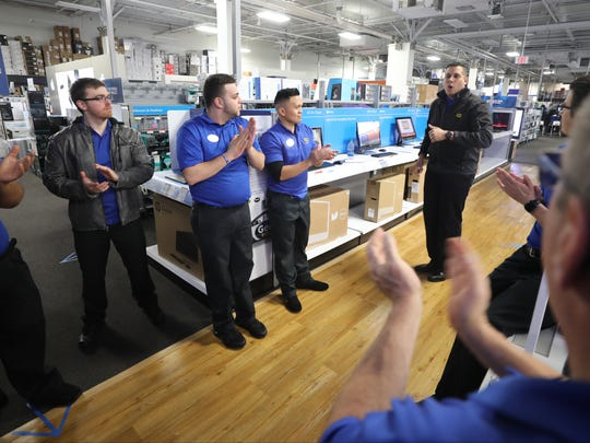 Marcel Gomez, the store's general manager, right, pumping up the computer team during Saturday's session.