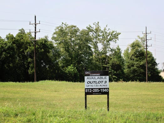 A real estate sign offers a large parcel for sale along