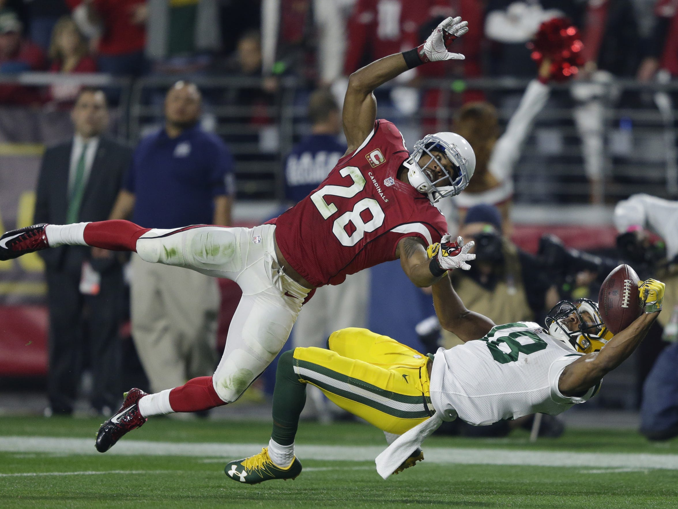 Green Bay Packers receiver Randall Cobb makes a leaping catch against Arizona Cardinals cornerback Justin Bethel in the first quarter. The catch was called back on off setting penalties and Cobb was injured on the play.