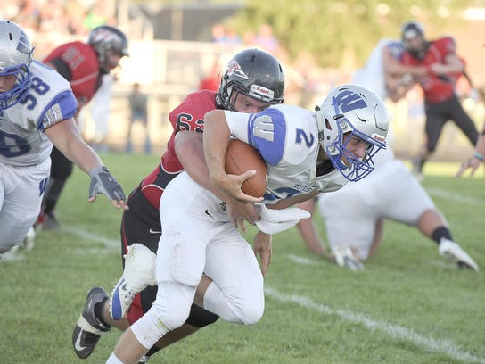 Wynford quarterback Zach Hoffman is slowed down by