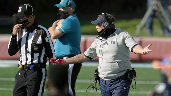 Patriots head coach Bill Belichick, right, appeals to down judge Kent Payne during the second half of Sunday's game against the Broncos.
