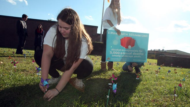 Pequannock Township High School student Ali Pierson places a pinwheel in front of the main entrance to the building during homecoming week, as part of the Morris County High School Pinwheel Prevention Project. October 15, 2015, Pequannock, NJ.