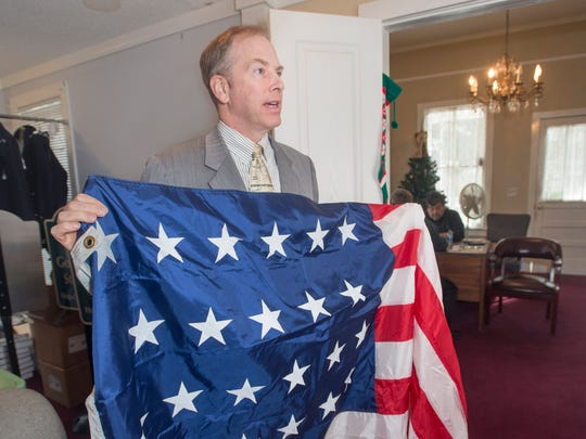 Go Retro owner Wesley Odom shows a replica of a 23-star American flag that was raised in Pensacola's Plaza Ferdinand VII when West Florida was transferred from Spain to the United States on July 17, 1821.  The Jacksonian Guard Color Ceremony will be adding Spanish troops when it reenacts the full ceremony starting this year.