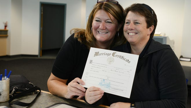 Barb Cooney (left) and Lisa Hill apply for a marriage license at the Marion County Clerk's Office in downtown Salem on Monday, May 19, 2014.