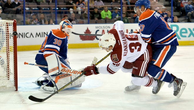 Oct 1, 2014: Arizona Coyotes left wing Rob Klinkhammer (36) takes a shot wide against the Edmonton Oilers goalie Ben Scrivens (30) in the first period at Rexall Place.