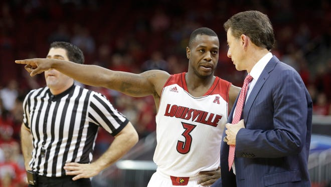 Louisville guard Chris Jones checks things out with coach Rick Pitino.December 4, 2013