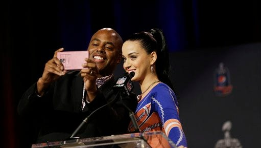 Katy Perry has a selfie taken with a reporter at a halftime news conference for NFL Super Bowl XLIX football game Thursday in Phoenix.