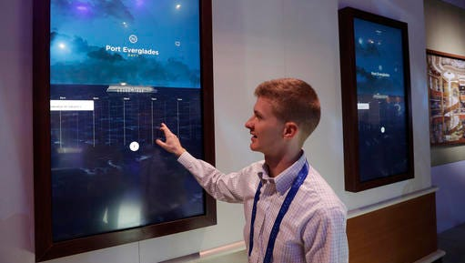 Miles Clark of Carnival Corp. demonstrates the Ocean Compass interface before CES International, Tuesday, Jan. 3, 2017, in Las Vegas. The linchpin of the concierge technology is a medallion the size of a quarter that passengers carry with them. The medallion uses wireless technologies to communicate with sensors placed around the ship and allows them to interact with displays around the ship or with crew members.