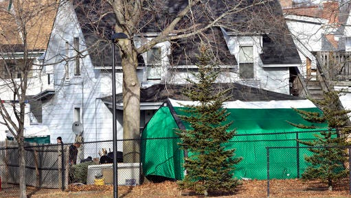 """FILE - In this Jan. 17, 2017 file photo, a large green tent is seen in the back of a house on Hayward Street in Manchester, N.H., where authorities searched for clues in the missing person's case of Denise Beaudin. State authorities said the case is connected to one involving four bodies found in two steel drums between 1985 and 2000 in a state park. Beaudin's family last saw her on Thanksgiving 1981, when she was 23, with her boyfriend, Robert """"Bob"""" Evans, and her infant daughter."""