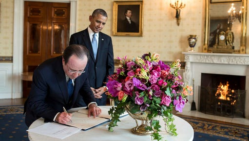 """In this Feb. 11, 2014 photo provided by Stichting Kunstboek, French President François Hollande signs the guest book as President Obama looks on at the White House in Washington. For the state visit, a centerpiece bouquet of early spring flowers in the French style is presented in a gilded pedestal Vermeil vase, part of the historic White House collection. The gloriosa lilies mimic the flames of the fire in the Blue Room. The photograph is featured in the book """"Floral Diplomacy: At the White House,"""" by Laura Dowling."""