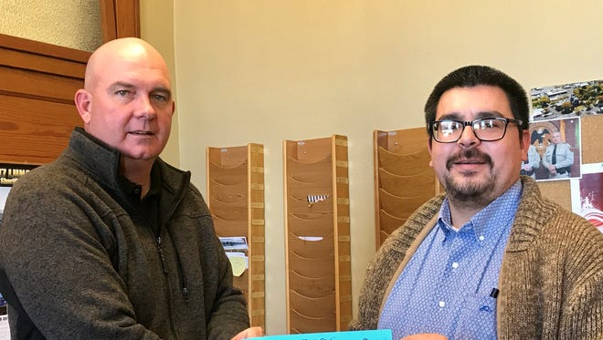Luna County Manager Ira Pearson, left, purchased the first ticket for the Deming-Luna County Humane Society Woofstock Cash Party. Selling the ticket is DLCHS President Matt Robinson.