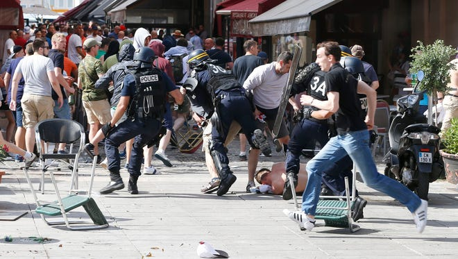 French police officers charge soccer supporters during clashes in downtown Marseille, France, Saturday, June 11, 2016.