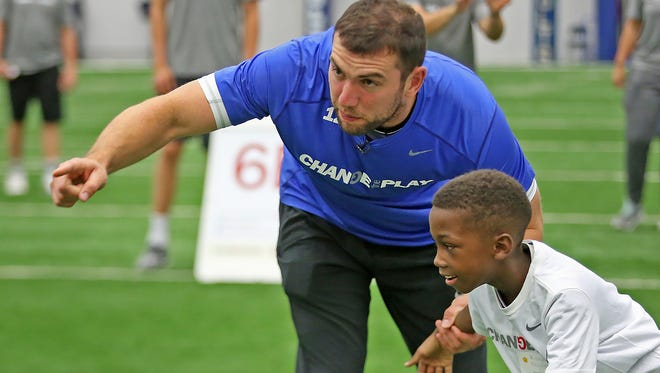 Colts quarterback Andrew Luck gives tips to Kevyn Milliner in the passing station at one of the Change the Play Camps held at the Indiana Farm Bureau Football Center.