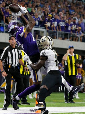 Minnesota Vikings wide receiver Stefon Diggs, left, catches a 2-yard touchdown pass over New Orleans Saints cornerback De'Vante Harris during the first half of an NFL football game, Monday, Sept. 11, 2017, in Minneapolis.