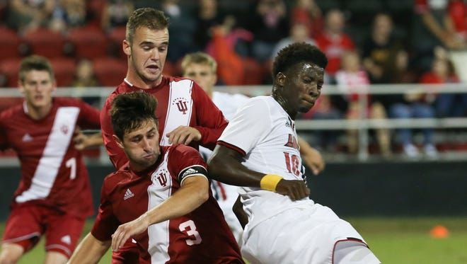 IU's Derek Creviston (3) and Andrew Gutman (15) battle U of L's Mohamed Thiaw (10) for possession during their match at Lynn Stadium.  IU defeated U of L 2-1.Oct. 11, 2016