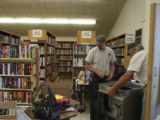 Shasta County mechanical craft worker Matt Berry, left, and supervising craft worker Nick Butrie install a new heating unit in the Burney Public Library in 2017.