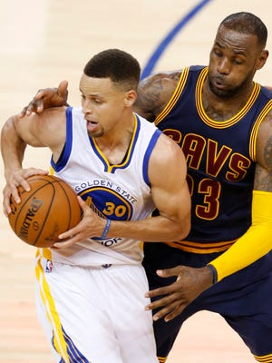 Cleveland Cavaliers forward LeBron James (R) plays defense against Golden State Warriors guard Stephen Curry (L) in Game 1.