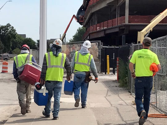 Workers leave the Little Caesar's Arena construction