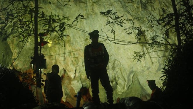 Thai police stand in front of the entrance to a cave complex where 12 boys and their soccer coach went missing, in Mae Sai, Chiang Rai province, in northern Thailand, Monday, July 2, 2018. Rescue divers are advancing in the main passageway inside the flooded cave in northern Thailand where the boys and their coach have been missing more than a week. (AP Photo/Sakchai Lalit)