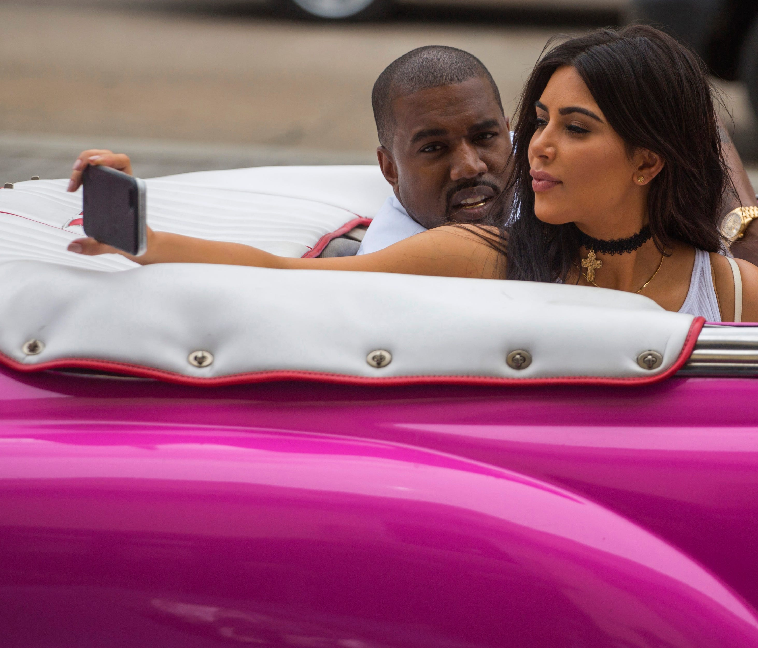 American reality-show star Kim Kardashian takes a selfie as she rides on a classic car next to her husband, rap superstar Kayne West in Havana, Cuba, in 2016