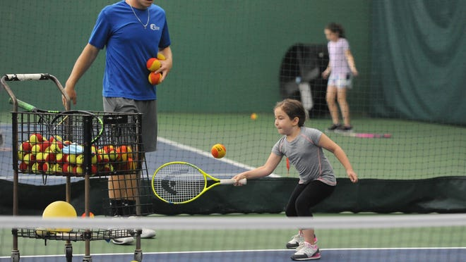 Instructor Sam Majewski helps Lylia Eloy, 6, of West Barnstable, during a tennis clinic Monday at Mid-Cape Athletic Club in South Yarmouth. Gyms and fitness centers closed for months during the coronavirus pandemic have been allowed to reopen under Phase 3 of the governor's plan to revive the economy.