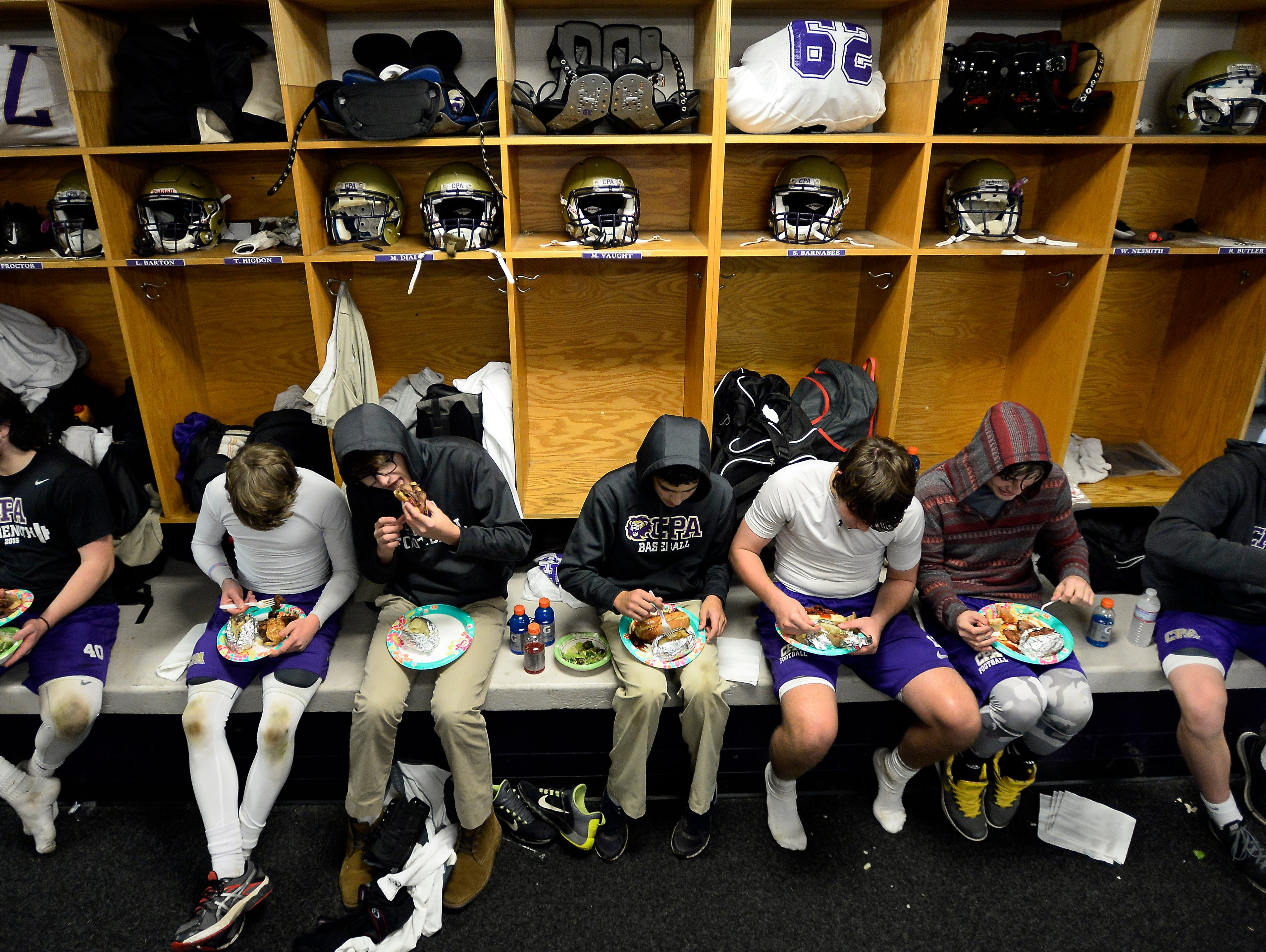 CPA football players enjoy an early Thanksgiving holiday team dinner in the Christ Presbyterian Academy football locker room after practice on Tuesday, Nov. 24, 2015 in Nashville, Tenn.