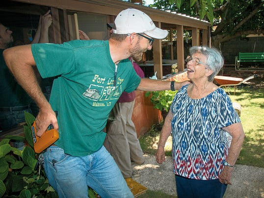 Jett Loe--Sun-News   Dustin Leonard talks with Pat Gill at her home which is being repaired with the help of the Both Hands organization.