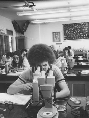 A student looks through a microscope in Western Carolina Unversity's natural science building not long after it opened in the 1970s. A bond proposal would raise money to replace it.