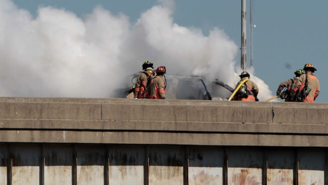 Cincinnati firefighters extinguish a vehicle fire at the north end of the Brent Spence Bridge on the ramp to Second Street.