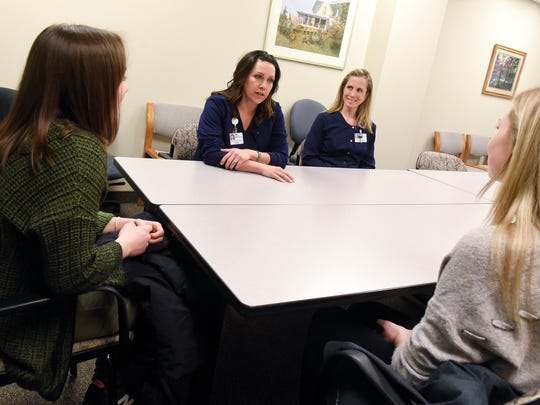 Naomi Baker and Maryann Burrows discuss careers in medical sonography with students Missy Prom and Rachel Merchlewicz Friday, March 23, at St. Cloud Hospital.